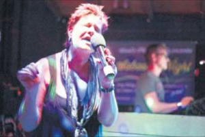 Barbara Tooten singing, accompanied by her husband Wolfgang in the background. (Photo The Daily Herald)
