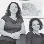 Dr. Jessica Vance Roitman (left) and PhD student Stacey Mac Donald of the Royal Netherlands Institute of Southeast Asian and Caribbean Studies KITLV in Leiden. In the background a historic photo of Saba's Fort Landing before the harbour was built. (Suzanne Koelega photo)