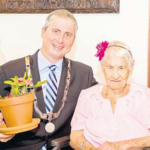 Island Governor Jonathan Johnson (left) wishes Edith Hassell-Lejunes a happy 100th birthday.