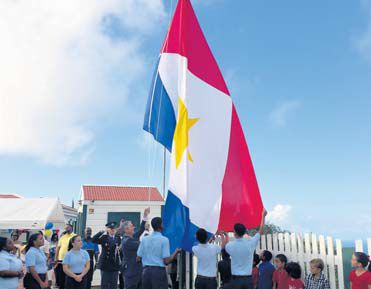 Island Governor Jonathan Johnson, assisted by students, hoisting the flag for Saba Day 2016.